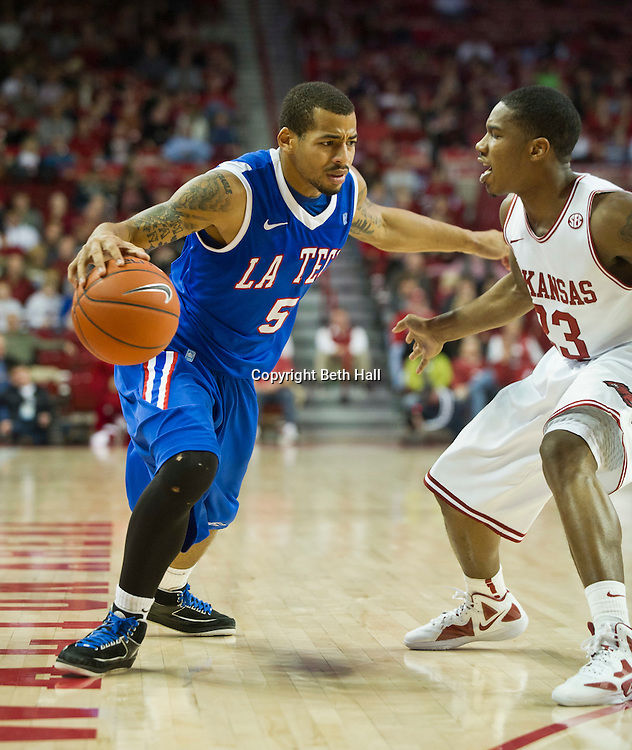Dec 22, 2011; Fayetteville, AR, USA; Louisiana Tech Bulldogs guard Trevor Gaskins (5) dribbles the ball against Arkansas Razorbacks guard Julysses Nobles (23) during a game at Bud Walton Arena. Arkansas defeated Louisiana Tech 75-63 Mandatory Credit: Beth Hall-US PRESSWIRE