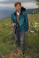 Portrait of wildlife photographer David Maitland in Galicica National Park, Macedonia, with northern shore of Lake Ohrid (693m) in background. View from Mount Baba at 1635 m above sea level. <br /> Galicica National Park, Macedonia, June 2009<br /> Mission: Macedonia, Lake Macro Prespa /  Lake Ohrid, Transnational Park<br /> David Maitland / Wild Wonders of Europe