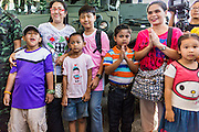 "11 JANUARY 2014 - BANGKOK, THAILAND: Thais stand in front of an armored vehicle during an Army open house on Children's Day. The Royal Thai Army hosted a ""Children's Day"" event at the 2nd Cavalry King's Guard Division base in Bangkok. Children had an opportunity to look at military weapons, climb around on tanks, artillery pieces and helicopters and look at battlefield medical facilities. The Children's Day fair comes amidst political strife and concerns of a possible coup in Thailand. Earlier in the week, the Thai army announced that movements of armored vehicles through Bangkok were not in preparation of a coup, but were moving equipment into position for Children's Day.      PHOTO BY JACK KURTZ"