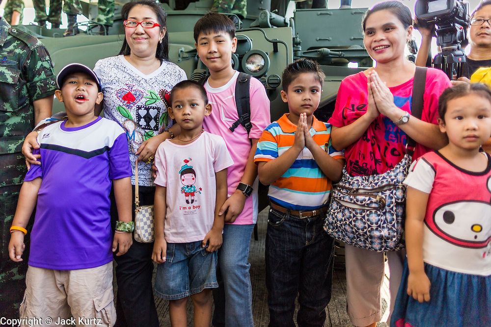 """11 JANUARY 2014 - BANGKOK, THAILAND: Thais stand in front of an armored vehicle during an Army open house on Children's Day. The Royal Thai Army hosted a """"Children's Day"""" event at the 2nd Cavalry King's Guard Division base in Bangkok. Children had an opportunity to look at military weapons, climb around on tanks, artillery pieces and helicopters and look at battlefield medical facilities. The Children's Day fair comes amidst political strife and concerns of a possible coup in Thailand. Earlier in the week, the Thai army announced that movements of armored vehicles through Bangkok were not in preparation of a coup, but were moving equipment into position for Children's Day.      PHOTO BY JACK KURTZ"""