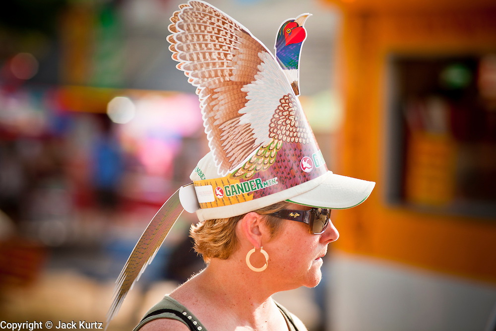 """01 SEPTEMBER 2011 - ST. PAUL, MN:  A woman wears a cut out pheasant hat from Gander Mountain, a Minnesota based sporting and outdoors retailer, at the Minnesota State Fair. The Minnesota State Fair is one of the largest state fairs in the United States. It's called """"the Great Minnesota Get Together"""" and includes numerous agricultural exhibits, a vast midway with rides and games, horse shows and rodeos. Nearly two million people a year visit the fair, which is located in St. Paul.   PHOTO BY JACK KURTZ"""