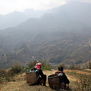 Black Hmong guides survey's the scene overlooking the highlands near Sapa close to the Chinese border in Northern Vietnam. The region is inhabited by highland minorities including Hmong and Dzao groups. Sapa is now a thriving tourist destination for travelers taking the night train from Hanoi. Sapa, Vietnam. 16th March 2012. Photo Tim Clayton