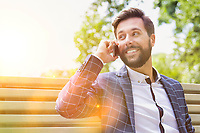 Portrait of young attractive businessman smiling while talking on smartphone
