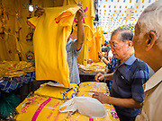 28 NOVEMBER 2014 - BANGKOK, THAILAND:  Men in Bangkok look tee shirts before the King's Birthday in Thailand. Bhumibol Adulyadej, the King of Thailand, was born on December 5, 1927, in Cambridge, Massachusetts. The family was in the United States because his father, Prince Mahidol, was studying Public Health at Harvard University. He has reigned since 1946 and is the world's currently reigning longest serving monarch and the longest serving monarch in Thai history. Bhumibol, who is in poor health, is revered by the Thai people. His birthday is a national holiday and is also celebrated as Father's Day. He is currently hospitalized in Siriraj Hospital, recovering from a series of health setbacks. Thousands of people come to the hospital every day to sign get well cards for the King. People wear yellow at events associated with the King because he was born on a Monday, and yellow is Monday's color in Thai culture. It's also the color of the monarchy.      PHOTO BY JACK KURTZ