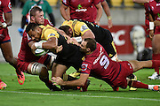 """Hurricanes' Ngani Laumape (L) scores a try as he is tackled by """"Reds' Curtis Browning and Nick Frisby with Hurricanes' Tony Lamborne in support during the Hurricanes vs Reds Super Rugby  match at the Westpac Stadium in Wellington on Saturday the 14th of May 2016. Copyright Photo by Marty Melville / www.Photosport.nz"""