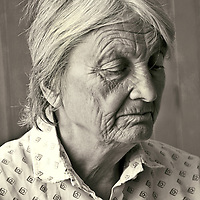 Pensive Woman with wrinkles looking away and down from the camera