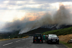 July 26, 2018 - Llangollen, Denbighshire, United Kingdom - People seen standing out for safety during the fire..Firefighters battled to put out a mountain Fire on hillside above the Horseshoe Pass in North east wales. There has been many recent outbreaks caused by a combination of extreme heatwave weather conditions and the criminal acts of arsonists. (Credit Image: © Andrew Mccoy/SOPA Images via ZUMA Wire)