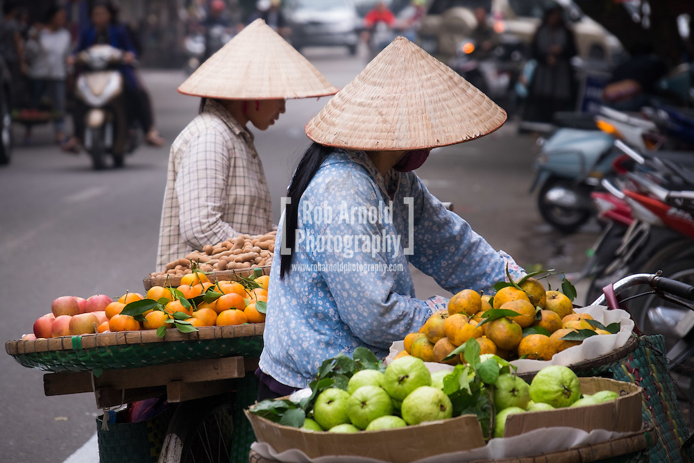 Street vendors selling fruit from the back of their bicycles in Hanoi's Old Quarter