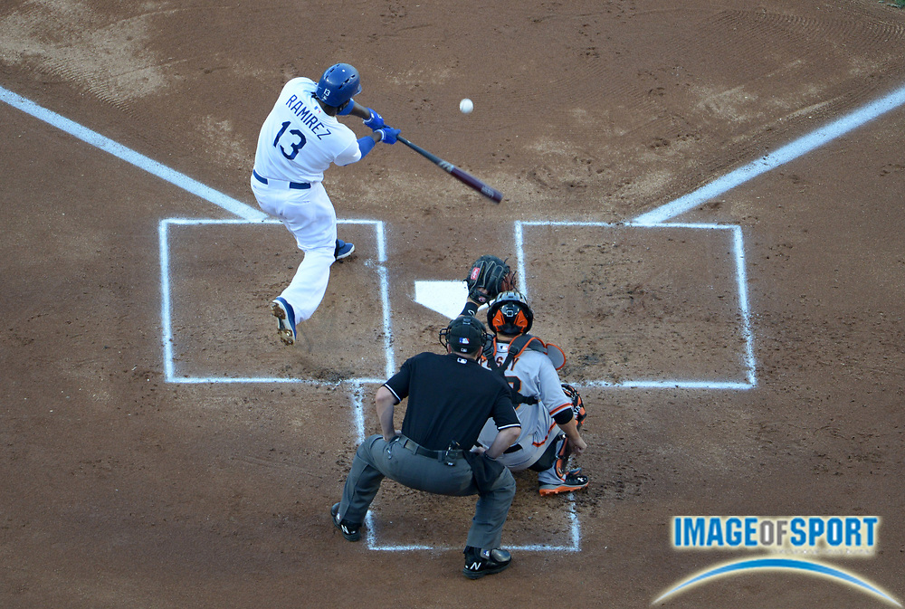 Apr 6, 2014; Los Angeles, CA, USA; Los Angeles Dodgers shortstop Hanley Ramirez (13) bats as San Francisco Giants catcher uster Posey (28) and home plate umpire Marty Foster (60) watch at Dodger Stadium. Ramirez hit two home runs in the Dodgers 6-2 victory.