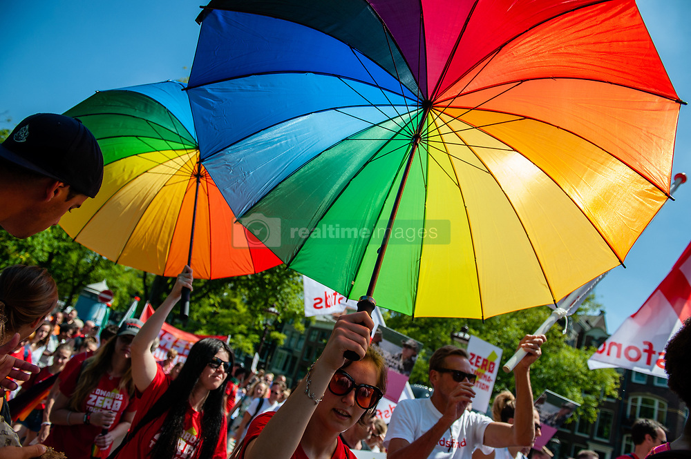 July 23, 2018 - Amsterdam, Netherlands - Hundreds of scientists and activists walk this Monday, July 23rd in Amsterdam during the AIDS March to demand access to HIV treatments. Access to healthcare and HIV treatment medication is still an ongoing issue affecting people everywhere, especially LGB, trans and intersex people, sex workers, indigenous people, young women, people who use drugs and many more vulnerable populations worldwide. Four activists from Australia, South Africa, and the UK embarked on an HIV awareness walk from Brussels Grand Place Sunday morning. They will spend 9 days walking to Amsterdam, which is 225 km away. They arrived in time for the 22nd International AIDS conference and also to walk the AIDS March. (Credit Image: © Romy Arroyo Fernandez/NurPhoto via ZUMA Press)