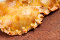 Group of Latin american empanadas over wooden plate. The Empanada is a pastry turnover filled with a variety of savory ingredients and baked or fried.