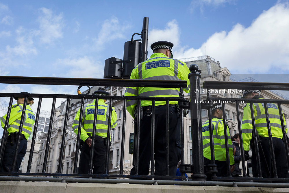 Met Police officers secure Oxford Circus during a Climate Change protest of the central London road junction and during an attempted occupation of Oxford Street, part of a two-week prolonged worldwide protest by members of Extinction Rebellion, on 18th October 2019, in London, England.