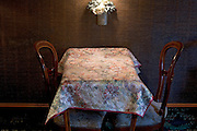 small table with 2 chairs against a wall with damaged wallpaper