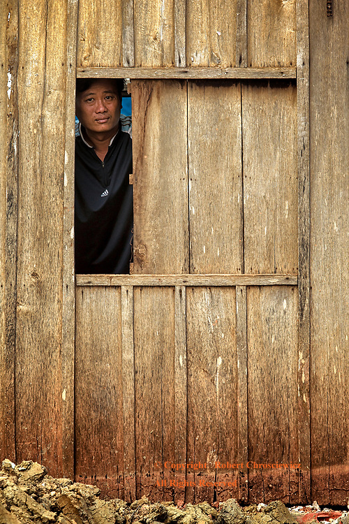 In Looking Out: A man pensively peers out of a building out to an adjacent construction site in Battambang Cambodia.