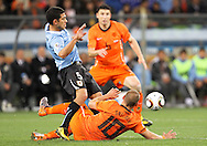 CAPE TOWN, SOUTH AFRICA- Tuesday 6 July 2010, Walter Gargano kicks the ball away from Wesley Sneijder during the semi final match between Uruguay and the Netherlands (Holland) held at the Cape Town Stadium in Green Point during the 2010 FIFA World Cup..Photo by Roger Sedres/Image SA