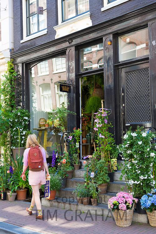 Shopper passes traditional florist shop in the Nine Streets - De Negen Straatjes - 9 Streets district of Jordaan, Amsterdam