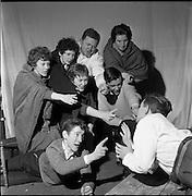 """05/04/1962<br /> 04/05/1962<br /> 05 April 1962<br /> Two plays at Damer Hall, Dublin for Gael-Linn. The plays were two Oireachtas prize-winning plays """"Na Mairnealaigh"""" by Eoghan O Tuairisc and """"Stailc Ocrais"""" by Mired Ni Ghrada. Image shows a scene from """"Stailc Ocrais"""", included are: Nuala Ní Dhónaill; Pádraig Ó Catháin; Deirdre Ní Dheasuin; Máiréad Ní Bhriain; Maire Ní Oistín; Brian Ó Badighill (Ó Baoill); Seosamh Ó Mongaidh; and Dónal Ó Cuill (Ó Coill) (on right)."""