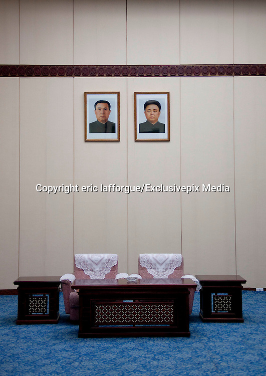 THE DEAR LEADERS ARE WATCHING YOU<br /> Anywhere you are in DPRK, you will see the portraits of the Dear Leaders. In the houses, in the offices, in the<br /> hospitals, in the subway, they never leave you!<br /> If you look carefully, you will see that they are the frames are leaning forward to avoid reflections that would<br /> make them difficult to see.<br /> Only the portraits of Kim Il Sung and Kim Jong Il can bee seen. Kim Jong Un has not yet portrait yet. They are<br /> sometimes accompanied by a portrait of Kim Jong Suk, Kim Il Sung's first wife, and the mother of Kim Jong Il.<br /> In this case they are dressed with military uniforms and caps.<br /> They are two versions, one with pictures from the 80's where the Leaders are very serious, one from the 90s<br /> where they smile. Some say they were the only people who smiled in North Korea.<br /> The portraits are so photshopped, in fact retouched by hand by north korean artists, that they look more ike<br /> paintings that pictures.<br /> The people who marry receive the two portraits and sometimes a third one showing Kim il Sung and Kim Jong Il<br /> chating with papers in the hands. This picture is really bad as it is taken with flash in a corridor office. When i<br /> asked my guide, he admitted this was not a perfect quality picture but it was the perfect illustration of the Dear<br /> Leaders working for the people, even when they were walking.<br /> When you ask north koreans if those portraits are not too much everywhere, they say that as they venerate the<br /> Leaders, it is a pleasure to see them all day long. My guide even noticed that many people have Jesus crucifix<br /> inside their bedrooms in western countries, for him, it was the same…<br /> The frames must always be clean, without fingers marks or dust for example. If you are caught not taking care<br /> of your portraits, you may have problems with the Party or even fined. I noticed that many portraits were dull<br /> because of the sun light on them after years, and were not changed. It seems it was a problem of budget.<br /> The wall where the portraits are hu