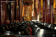 Rows of black bowls are lined up on a table at a wooden temple in Chiang Mai, Thailand.