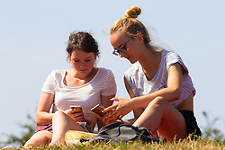 Friends Paulina Michor, 21, right, and Alex Szyszko, 23 a view of the capital's skyline in the hot sunshine on Primrose hill in North London. London, August 06 2018.