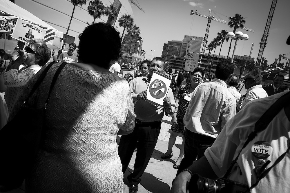"""""""Congratulations! Have you registered to vote?"""" shouts a Republican party activist, left, as Democratic party activist Reynoldo Lopez confronts the new Americans with a anti-Trump sign. Both political parties set up tables immediately outside the ceremony where they battle to register them in time to vote in the 2016 election. The LA Times reported a 32% increase in citizenship applications over the same time last year."""
