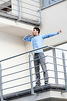 Full length of young businessman stretching at hotel balcony