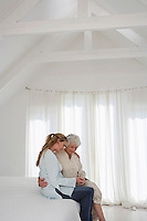 Mother and adult daughter sitting on bed in bedroom