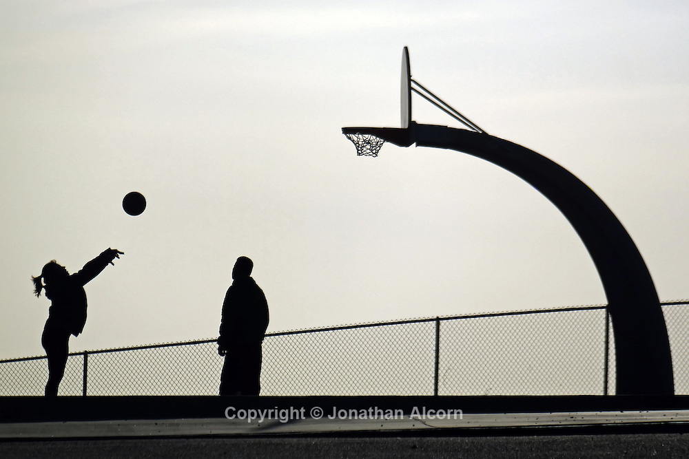 A woman takes a shot on a basketball court at San Pedro's Friendship Park