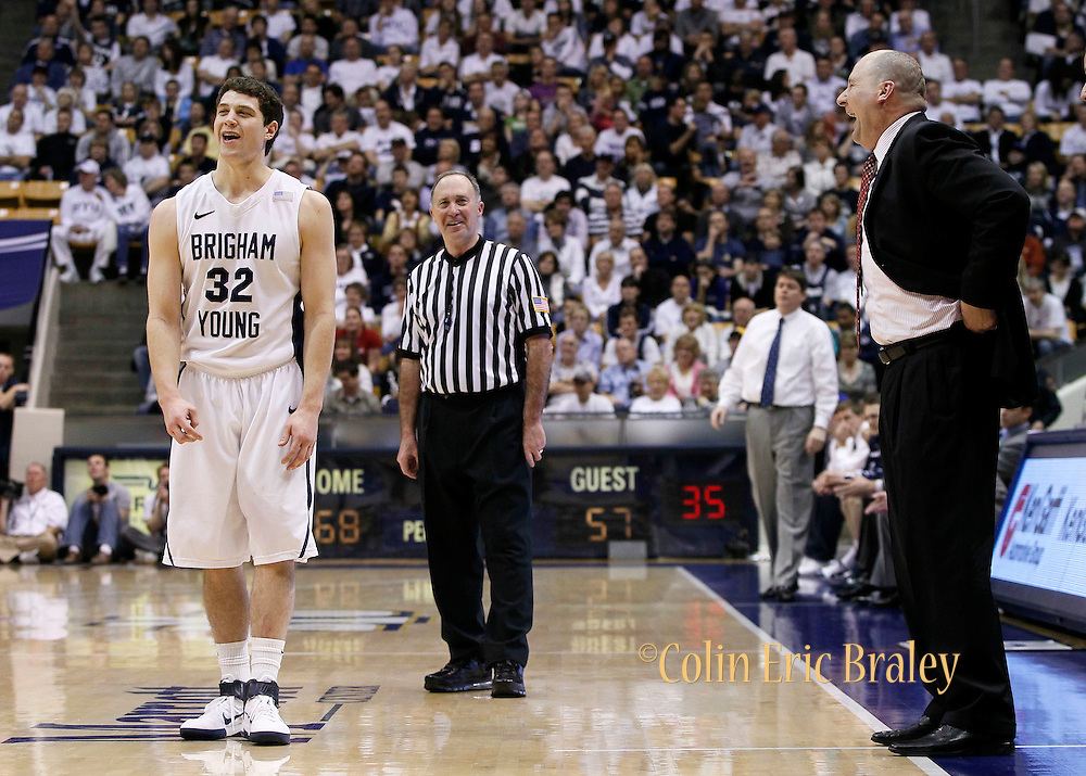 BYU guard Jimmer Fredette (32) and Utah head coach Jim Boylen, right, joke as BYU leads late in the second half of an NCAA college basketball game in Provo, Utah, Saturday, Feb. 12, 2011. BYU defeated Utah 72-59.(AP Photo/Colin E Braley)