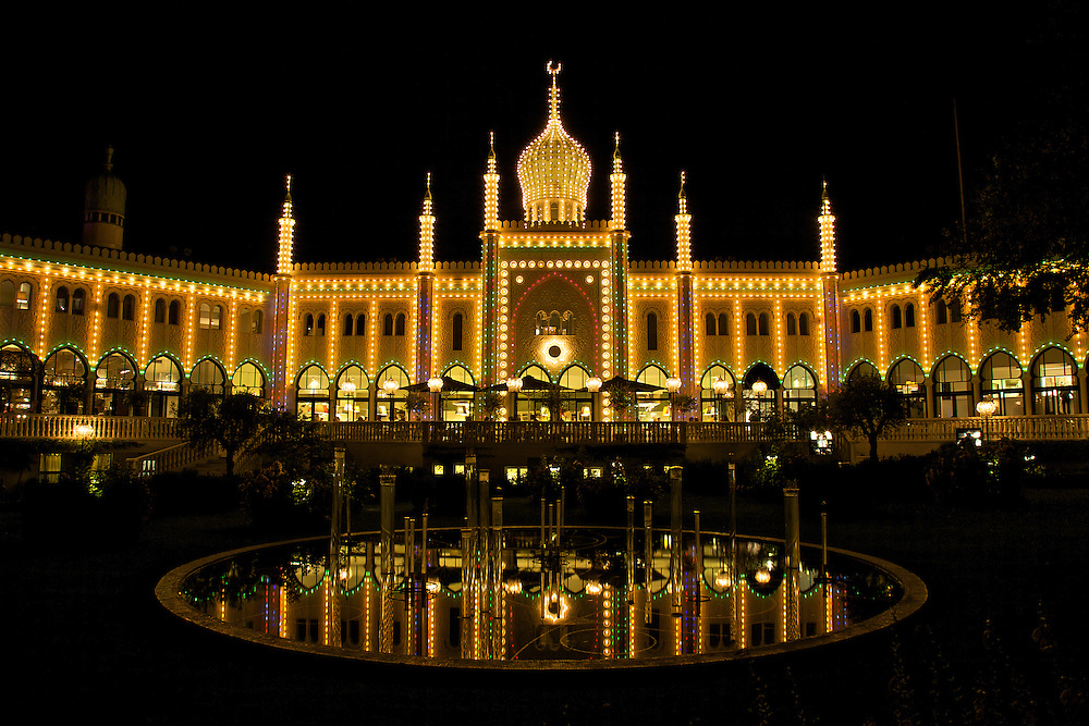 The iconic Nimb hotel and restaurant on the grounds of Tivoli Gardens in Copenhagen displays lights and reflections at night. Tivoli Gardens is one of the oldest amusement parks in the world.
