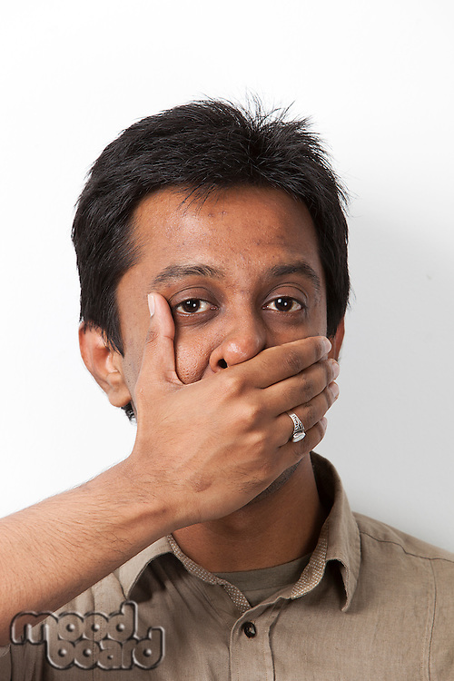 Portrait of young Indian man covering his mouth against white background