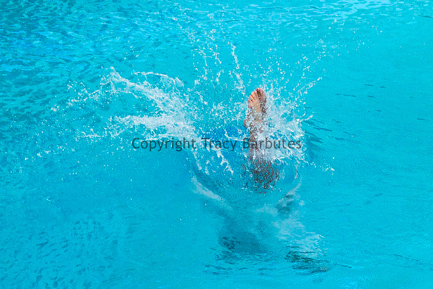 A member of the Stanford University Swimming and Diving team enters the water during diving competition