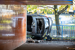 © Licensed to London News Pictures. 27/10/2019. Salford, UK. A car lies on its side on a pedestrian walkway at the Pendleton Roundabout on Broad Street in Salford . Members of the public pulled a man and a woman from the wreckage after a BMW car crashed through a barrier and landed on a pedestrian underpass below . Their condition is unknown and police , paramedics and fire crews are at the scene . Photo credit: Joel Goodman/LNP