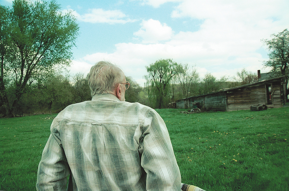 older man sitting  in field