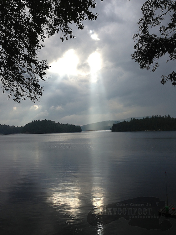 A beam of sunlight breaks through storm clouds and sends a shaft of light onto the waters of Tupper Lake in Adirondack Park near the town of Tupper Lake, New York.  Photo by Gary Cosby Jr.