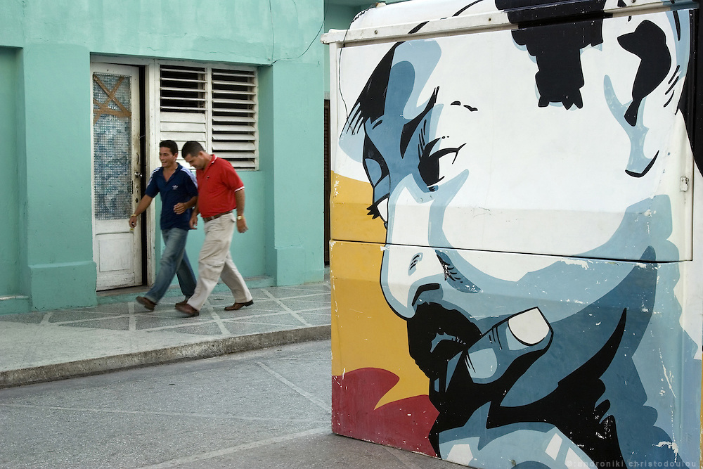 Men passing by a graffiti in Cienfuegos - CUBA