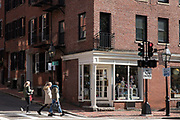 Street scene of people walking, shops, traffic and traffic lights - in historic district of Charles Street, city of Boston, USA