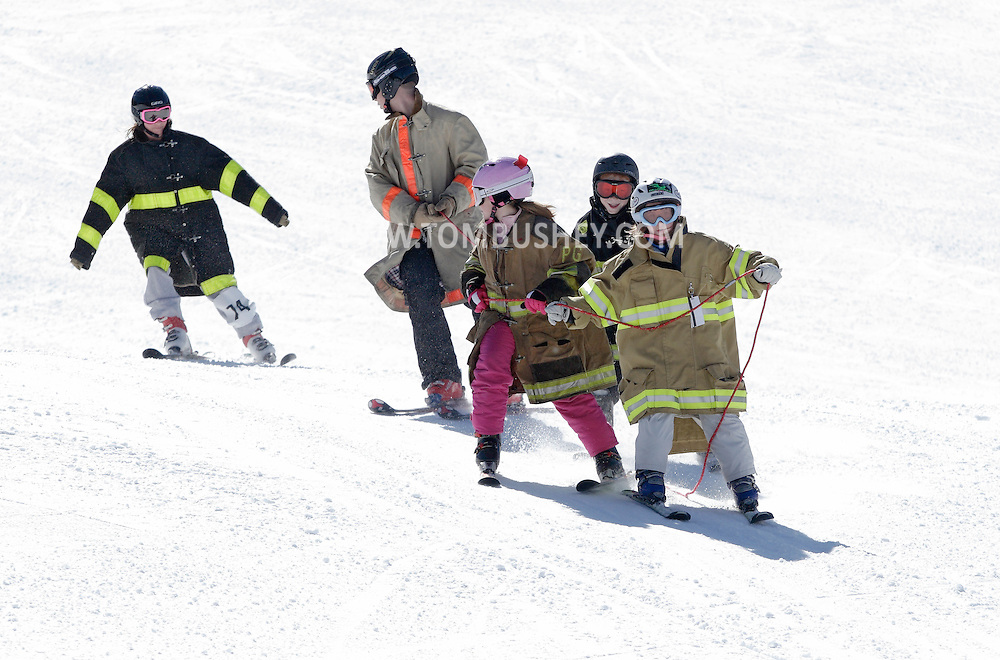 Bridgeville, New York - A team of young skiers wearing firefighter's coats heads down a course at Holiday Mountain during the firemen's races on March 6, 2010.