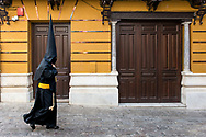 "A penitent walks in a street of Seville. On the building writing in Latin go: ""Hail Mary, full of grace, the Lord is with thee"". Andalusia, Spain"