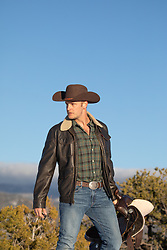 rugged cowboy walking with a saddle by a mountain range