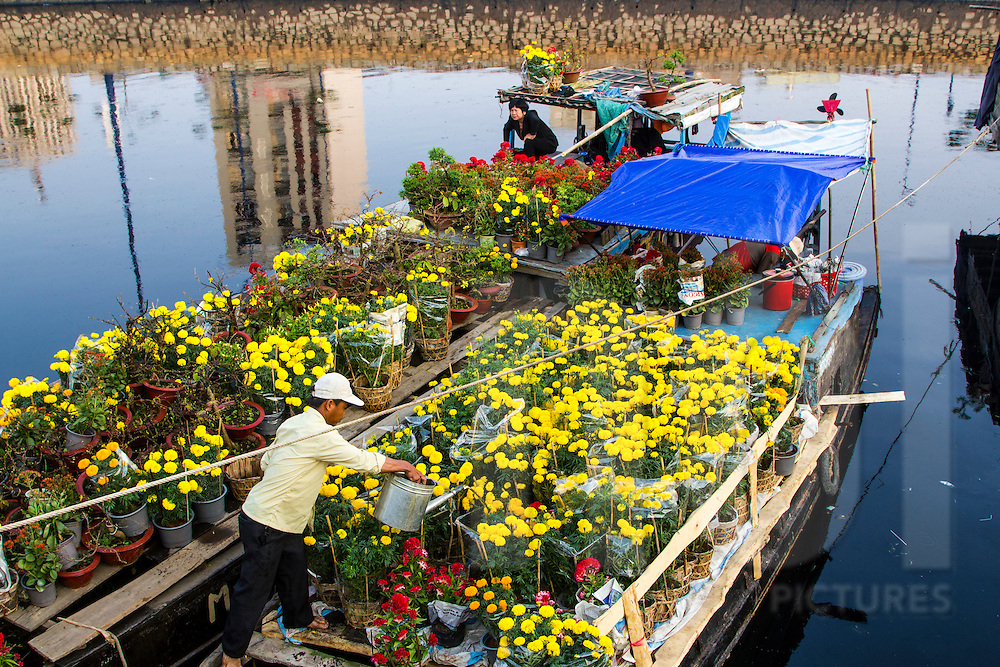 Vietnamese man waters bouquets of flowers for sale on a boat in a floating flower market in District 6 of Ho Chi Minh City, Vietnam, Southeast Asia
