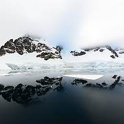 Mountains partially covered in ice and snow are reflected on perfectly still mirror-like waters in the Lemaire Channel on the western coast of the Antarctic Peninsula.