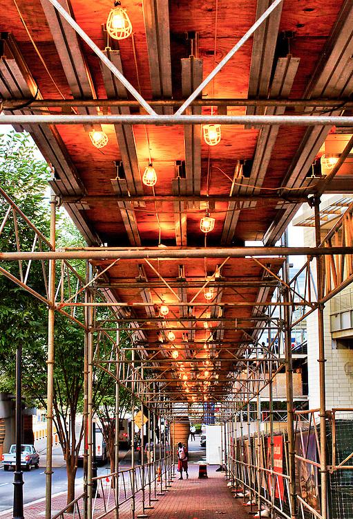 Orange lit scaffolding on a sidewalk in downtown Charlotte, North Carolina.