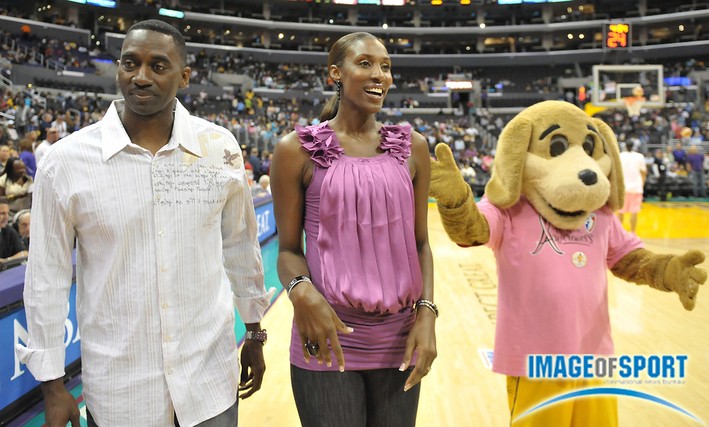 Aug 10, 2010; Los Angeles, CA, USA; Los Angeles Sparks former player Lisa Leslie (center) is accompanied by husband Michael Lockwood (left) and mascot Sparky during a halftime ceremony to retire the No. 9 jersey of Leslie during the WNBA game against the Indiana Fever at the Staples Center. Photo by Image of Sport