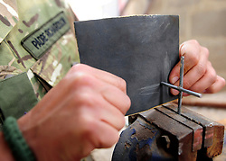 "© licensed to London News Pictures. HELMAND, AFG  21/04/11. The crosses are finished off in the workshop. A British Army chaplain from Sidmouth who is due to finish his tour this Easter Sunday has proved a hit with paratroopers in Helmand Province, handing out crosses made from the wire-mesh that surrounds their base. Padre Robin Richardson (40) a member of 3rd Battalion The Parachute Regiment, has been serving in Afghanistan for the last six months. ""Towards the beginning of the tour, some of the lads asked me if I had some crosses I could give them,"" he said. ""I found a few at Camp Bastion, and I gave them out. I ran out very quickly.""..""So I wandered around our camp at Shahzad, trying to find something I could fashion into a cross. I noticed some discarded Hesco wire, and I saw lots and lots of crosses"". The wire normally makes up part of the Hesco Bastion fortified walls,  mesh containers with thick liners filled with gravel - that surround military bases across Afghanistan. ""I got busy with some bolt-cutters and a hammer and a drill,"" said Robin. ""And I started making small crosses out of the discarded wire.""..""A lot of the lads have asked if they can have one,"" he said. ""And they've been wearing them, and understanding a bit about what lies behind it"". Robin will be returning home to be reunited with his family after six months. ""I've got three sons, aged 13, 11 and 7, and they're fab,"" he said. ""They give my heart a reason for beating every morning"". ""The thing I've missed the most has been their smiles"" he added. ""The first thing I'll do when I get home is give them a hug"".. Please see special instructions for usage rates. Photo credit should read SGT Alison Baskerville/LNP"