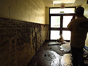 Former Nicholas County board of education member, Dr. Lloyd Adkins, in the hallway of Richwood Middle School the morning following the flood. The school has since been condemned along with the high school.  Photo by Jeromy Rose.