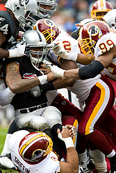 December 13, 2009; Oakland, CA, USA;  Oakland Raiders running back Darren McFadden (20) is tackled by Washington Redskins linebacker Rocky McIntosh (52) and defensive end Andre Carter (99) during the first quarter at Oakland-Alameda County Coliseum.  Washington defeated Oakland 34-13.