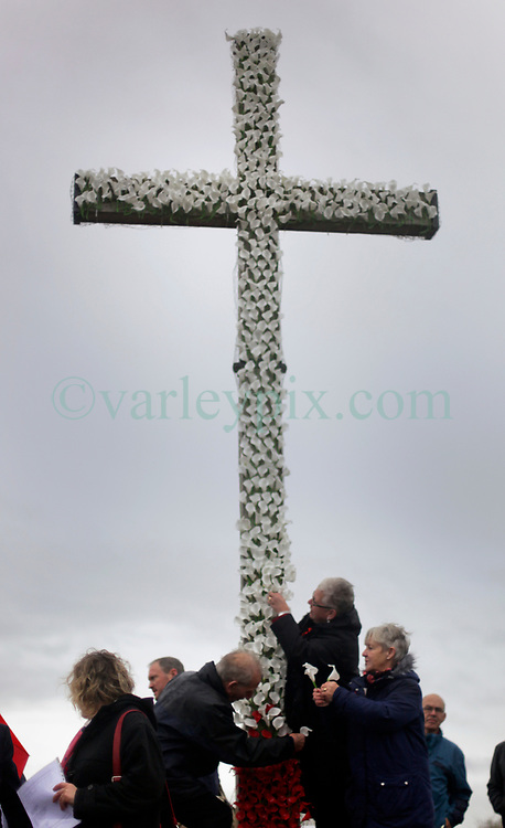 11 November 2018. Lochnagar Crater, La Boisselle, Somme, France. <br /> <br /> Gathered in the pouring rain, volunteers add lollies to the cross in honour of those who perished in the Great War. They are remembered by British and French civilians on the 100th anniversary of the Great War. <br /> <br /> Lochnagar Crater was created by the Tunnelling Companies of the Royal Engineers under a German field fortification. The explosion was the loudest man made noise created at that time, purportedly heard in London. <br /> <br /> Photo©; Charlie Varley/varleypix.com