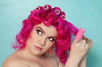 Young woman removing hair curlers over colored background