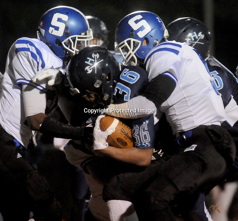Hoggard's Keevin Thompson is tackled by Scotland's Ty McLauren, left, and Brandon McMillian Friday November 28, 2014 at Hoggard High School in Wilmington, N.C. (Jason A. Frizzelle)